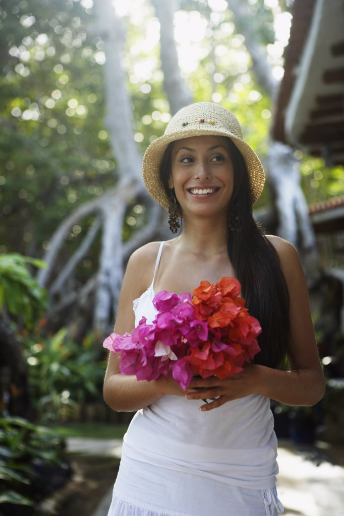 South American woman carrying bouquet of flowers : Stock Photo
