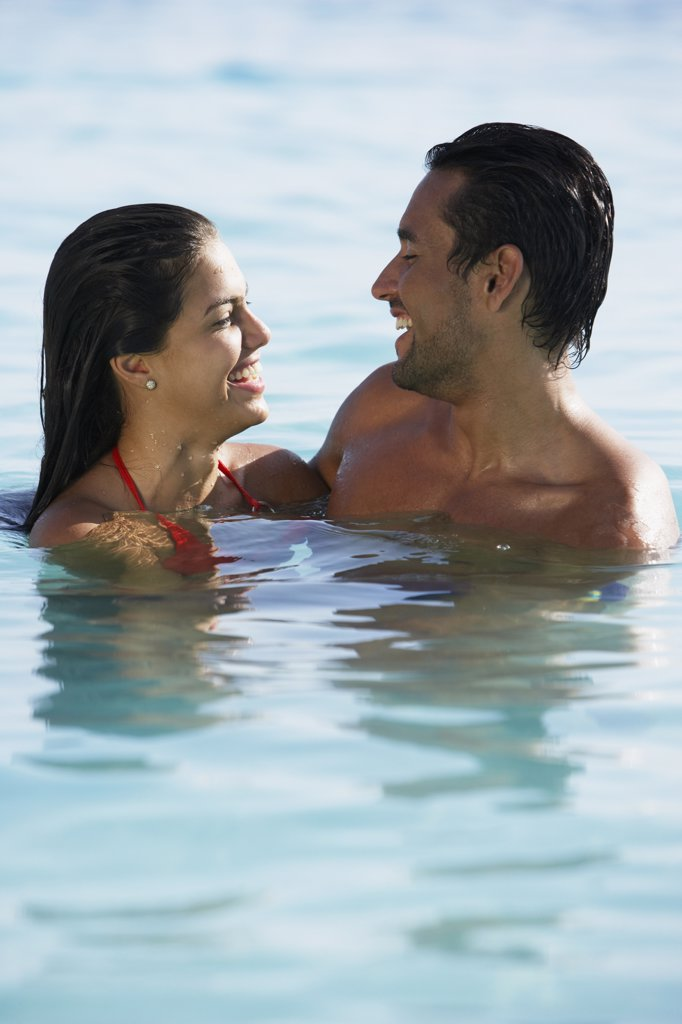 South American couple smiling at each other in water : Stock Photo