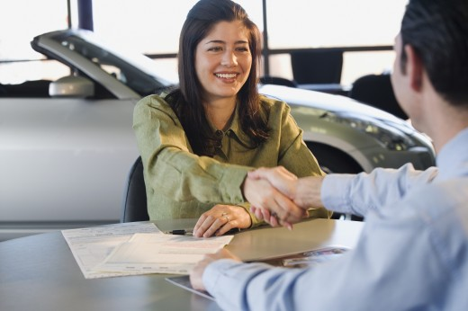 Woman shaking hands with car salesman : Stock Photo