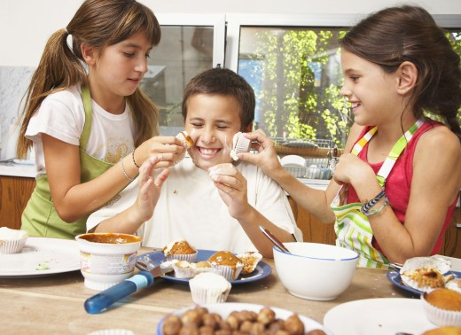 Hispanic siblings decorating cupcakes and being silly : Stock Photo