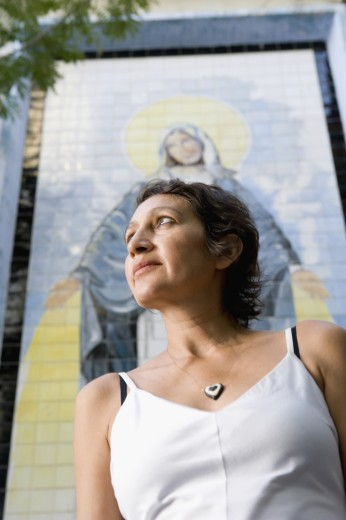 Stock Photo: 1589R-42472 Hispanic woman in front of Virgin Mary mosaic