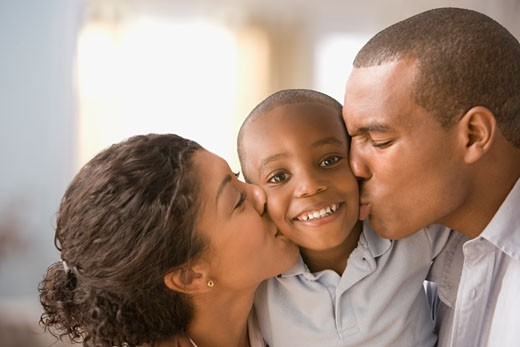 African American parents kissing son on cheeks : Stock Photo
