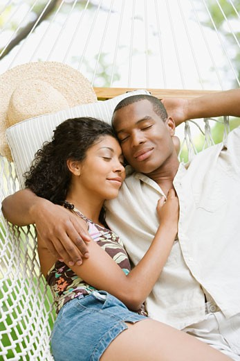 African American couple sleeping in hammock : Stock Photo