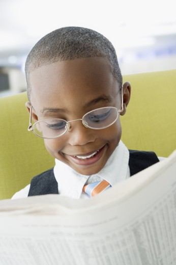 Stock Photo: 1589R-42749 African American boy reading newspaper