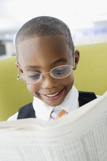 African American boy reading newspaper : Stock Photo