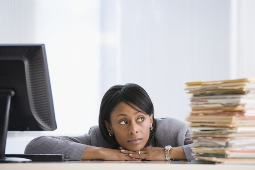 Stock Photo: 1589R-42825 African American businesswoman looking at stack of paperwork