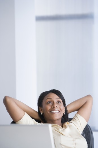 African American businesswoman with hands behind head : Stock Photo