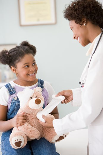 African American female doctor bandaging girl's teddy bear : Stock Photo