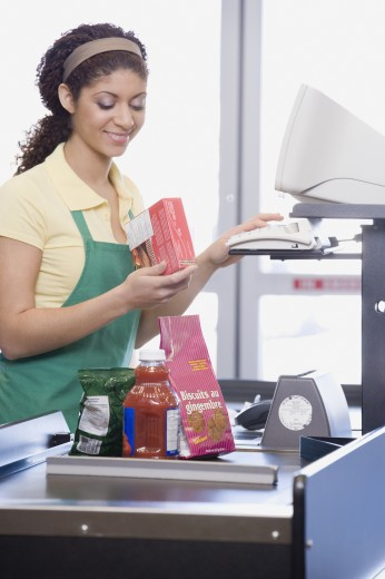 Stock Photo: 1589R-43277 Mixed Race female grocery clerk ringing up items
