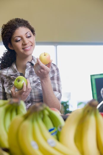 Mixed Race woman choosing apples at grocery store : Stock Photo