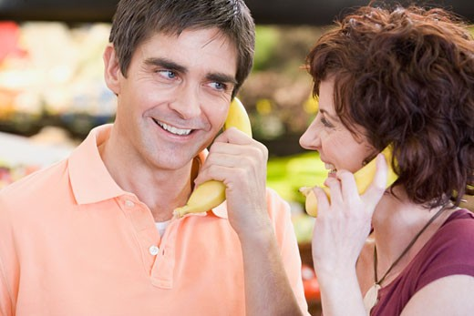 Stock Photo: 1589R-43303 Couple playing with bananas at grocery store