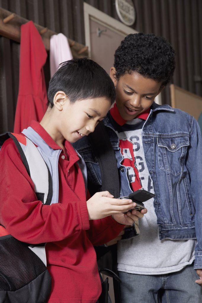 Multi-ethnic school boys looking at cell phone : Stock Photo
