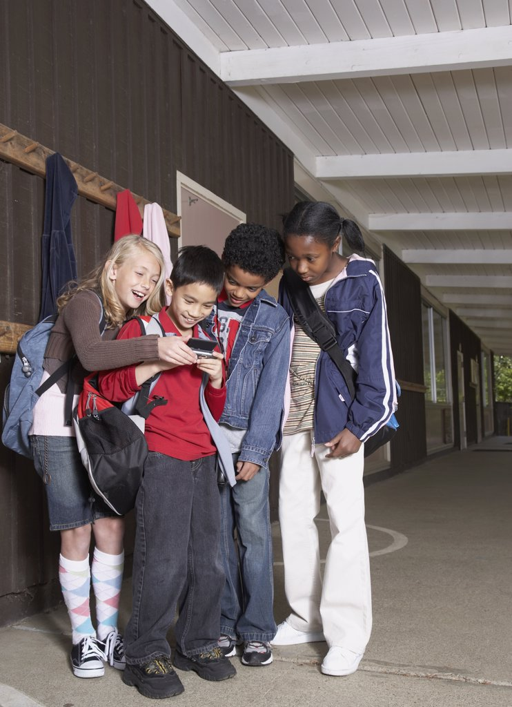 Multi-ethnic school children looking at cell phone : Stock Photo