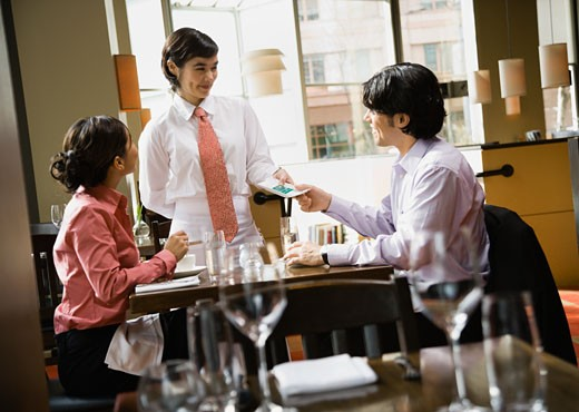 Stock Photo: 1589R-43524 Asian couple paying bill at restaurant
