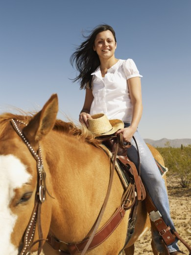 Hispanic woman riding horse : Stock Photo