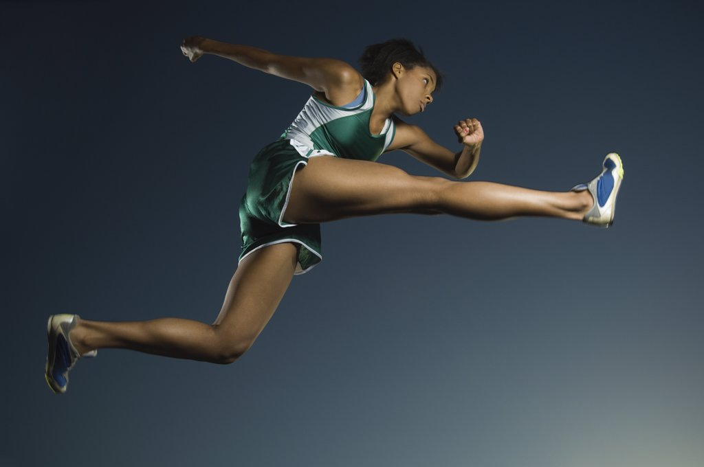 Stock Photo: 1589R-43875 African American female athlete jumping