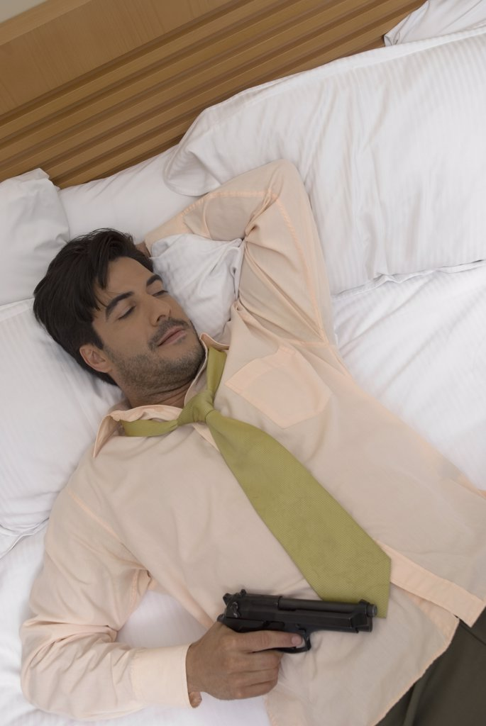 Stock Photo: 1589R-44010 Hispanic businessman holding gun in bed