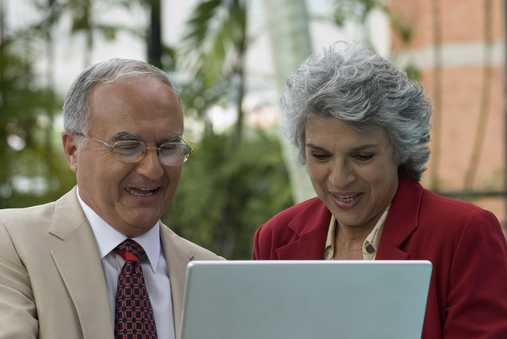 Senior Hispanic couple looking at laptop : Stock Photo