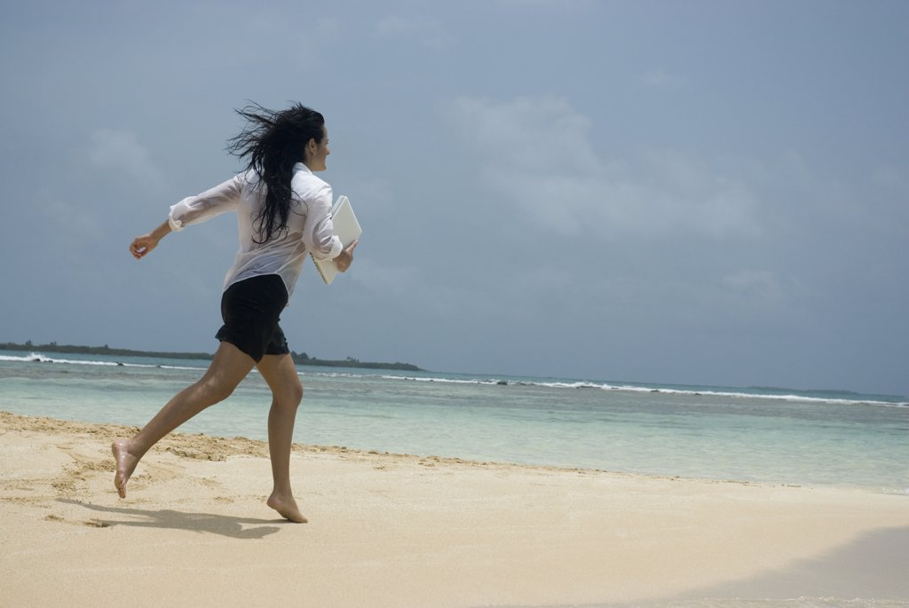 Hispanic woman running on beach : Stock Photo