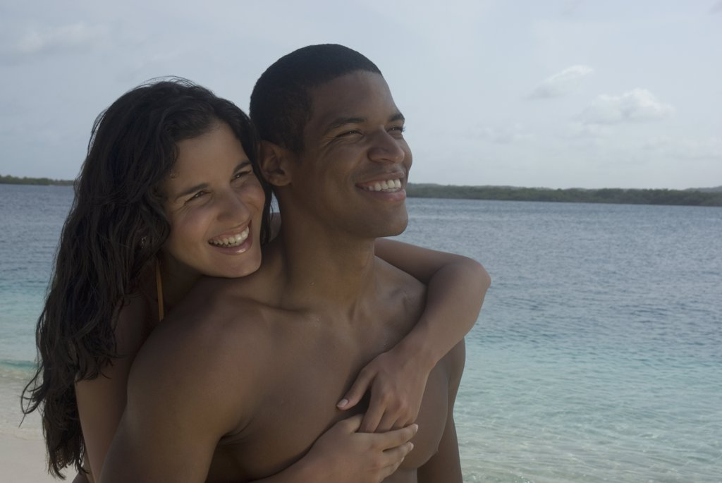 Stock Photo: 1589R-44212 Hispanic couple hugging at beach