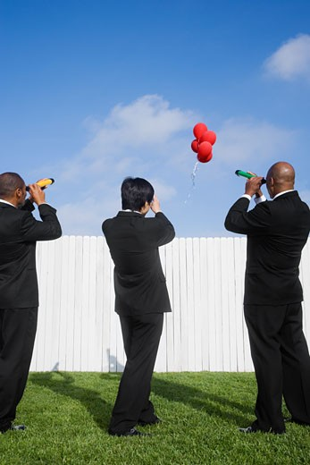 Multi-ethnic businessmen looking over fence at balloons : Stock Photo