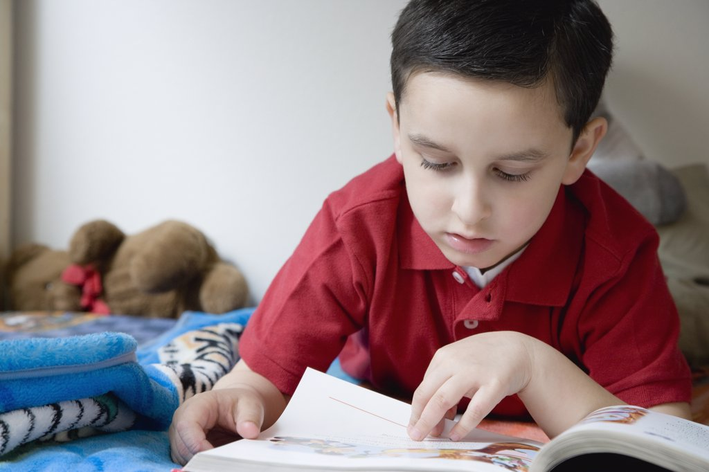 Stock Photo: 1589R-44484 Hispanic boy reading book