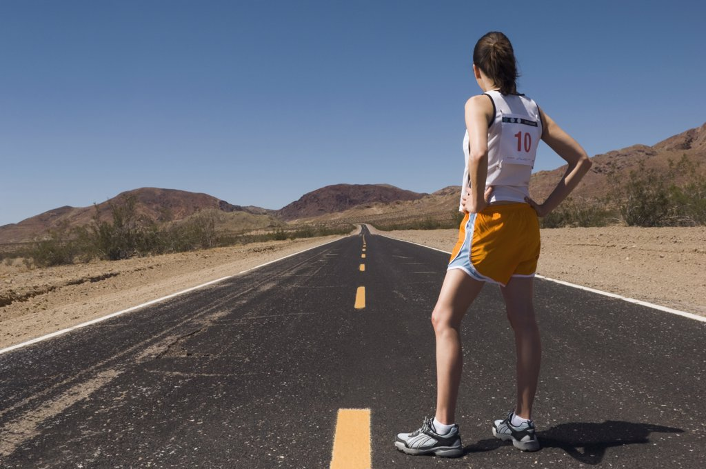 Mixed Race female runner on road : Stock Photo