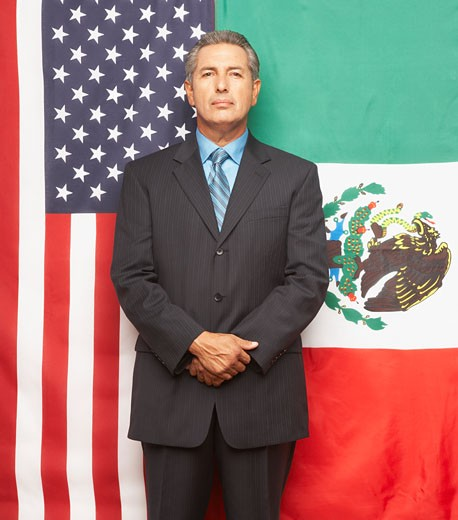 Hispanic businessman in front of American and Mexican flags : Stock Photo