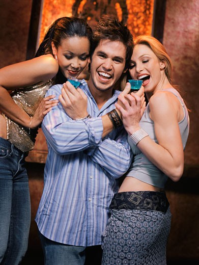 Stock Photo: 1589R-45001 Mixed Race man giving drinks to women at nightclub
