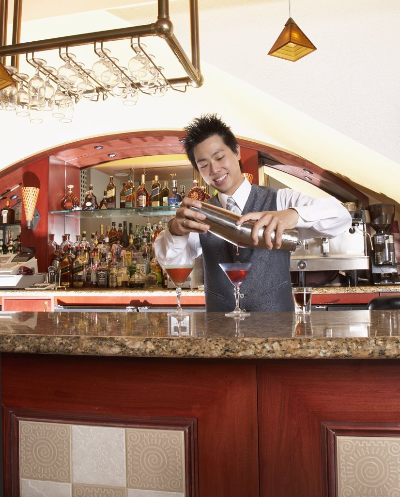 Asian male bartender pouring cocktails : Stock Photo