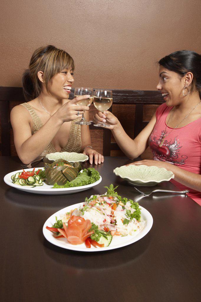 Multi-ethnic women toasting at restaurant : Stock Photo