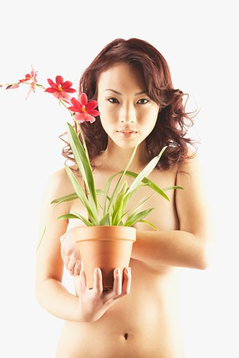 Stock Photo: 1589R-45297 Nude Asian woman holding potted plant