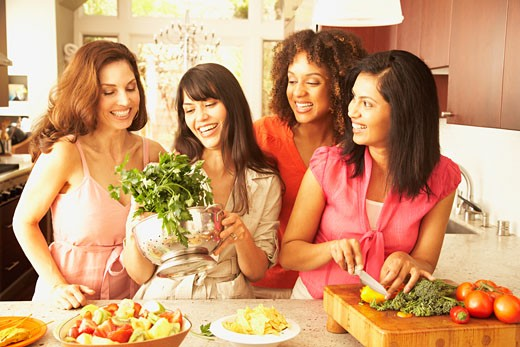 Multi-ethnic female friends preparing food : Stock Photo