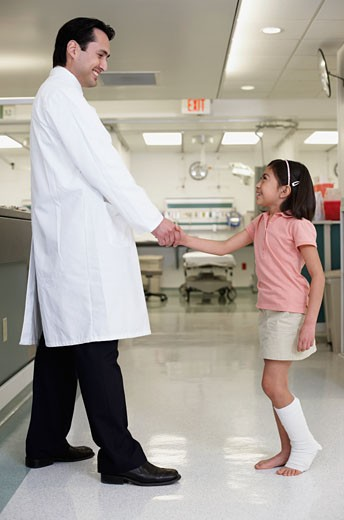 Hispanic girl shaking hands with doctor : Stock Photo