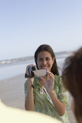 Stock Photo: 1589R-45673 Hispanic girl video recording people at beach