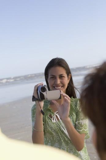 Hispanic girl video recording people at beach : Stock Photo