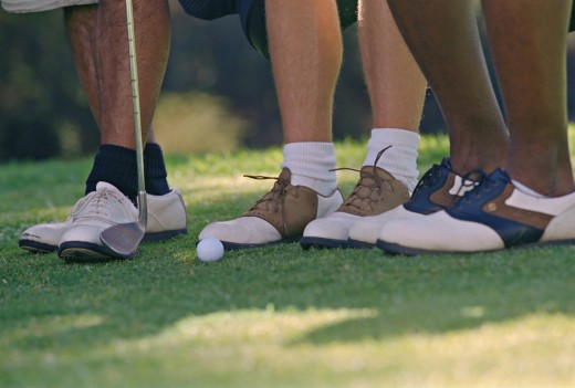 Close up of men's feet on golf course : Stock Photo