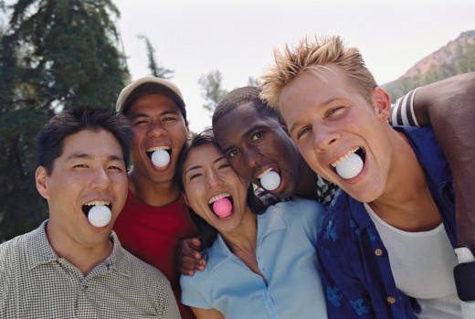 Multi-ethnic friends with golf balls in mouths : Stock Photo