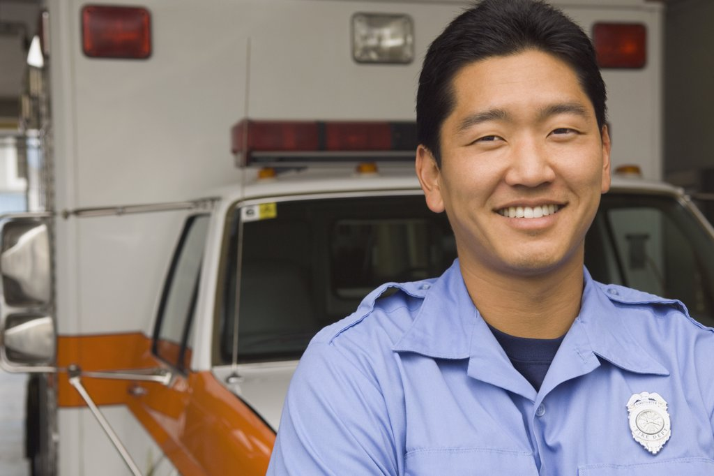 Stock Photo: 1589R-46007 Asian male paramedic in front of ambulance
