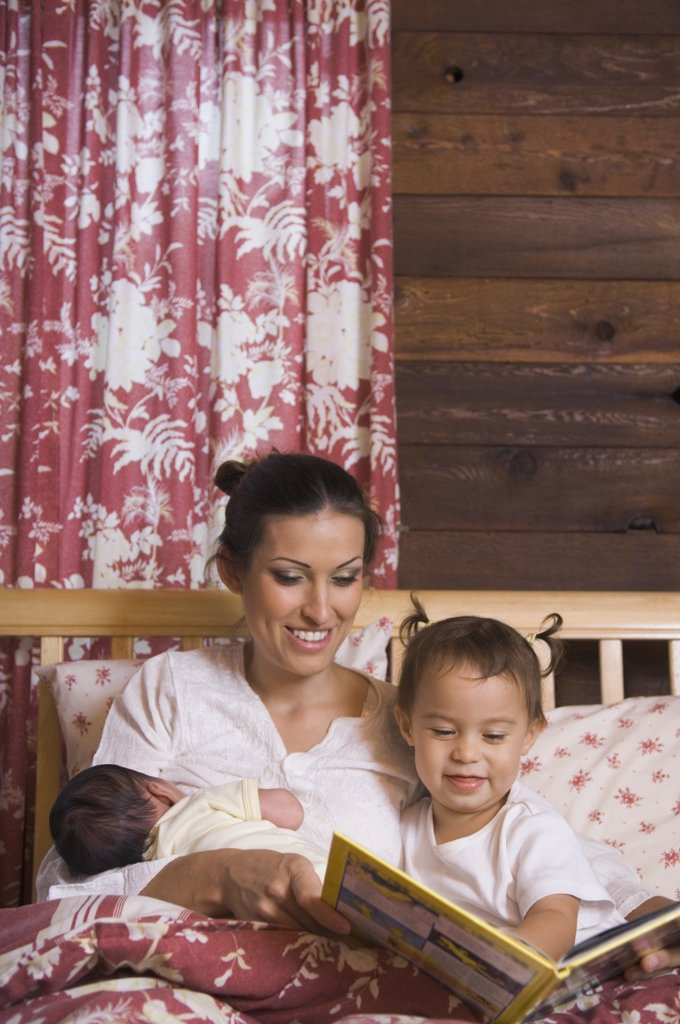Stock Photo: 1589R-46034 Hispanic mother reading to daughter