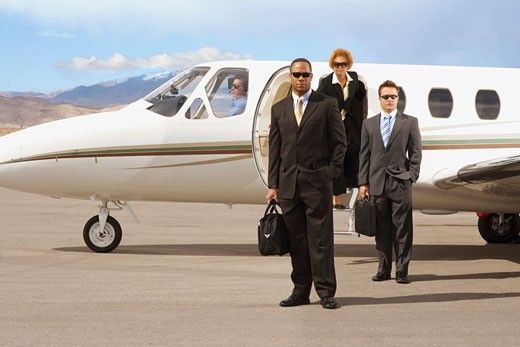 Stock Photo: 1589R-46116 Multi-ethnic businesspeople in front of airplane