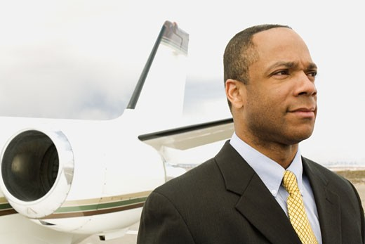 African businessman next to airplane : Stock Photo