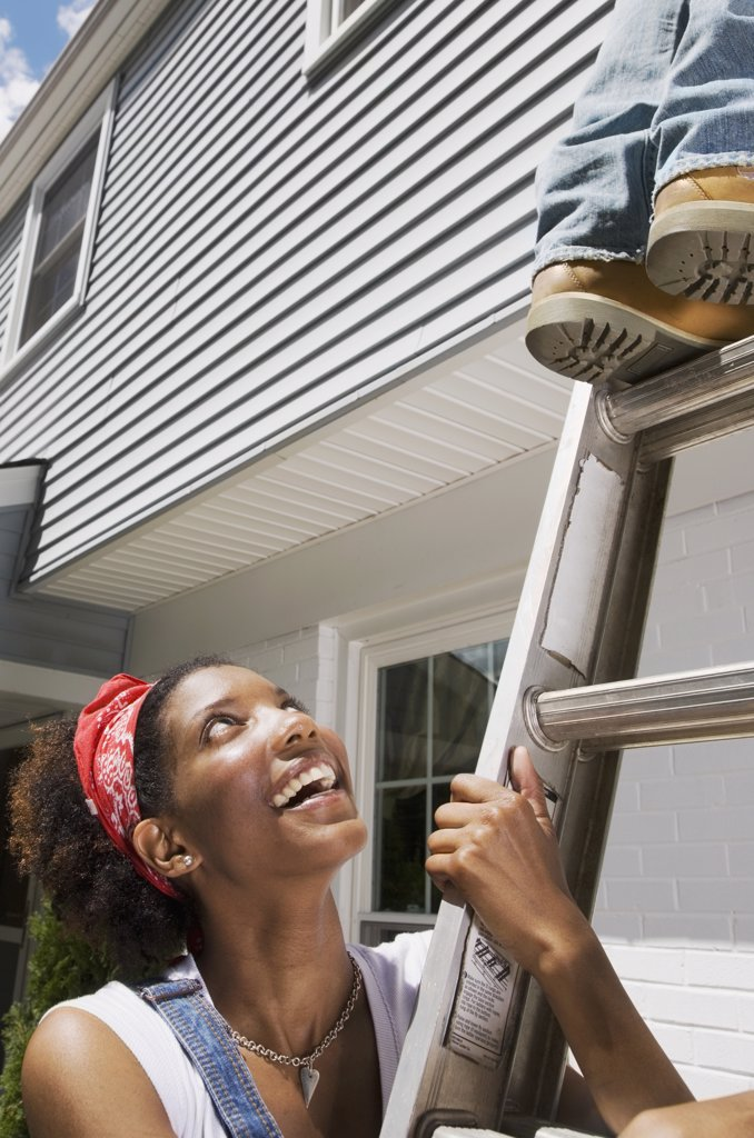 Stock Photo: 1589R-46211 African American woman holding ladder