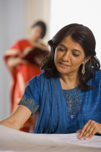 Stock Photo: 1589R-46337 Indian businesswoman looking at blueprints