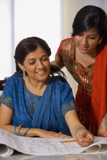Indian businesswomen looking at blueprints : Stock Photo