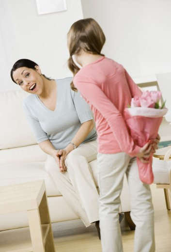 Hispanic girl surprising mother with flowers : Stock Photo