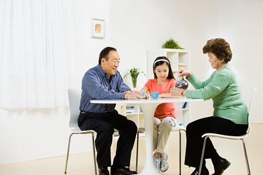Stock Photo: 1589R-46640 Asian grandparents and granddaughter having tea