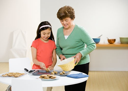 Stock Photo: 1589R-46642 Asian grandmother and granddaughter making cookies