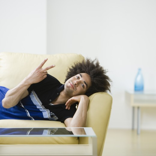 Mixed Race man laying on sofa : Stock Photo