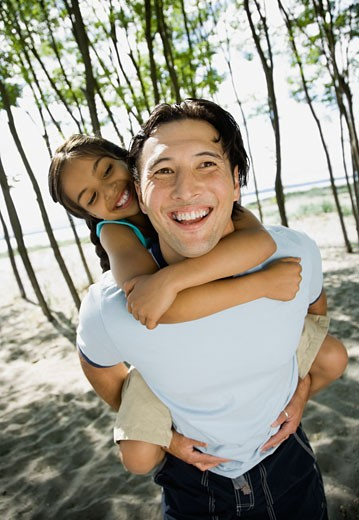 Stock Photo: 1589R-46865 Mixed Race father giving daughter piggyback ride